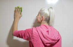 Eine kaukasische junge Hausgehilfin, die ein Badezimmer säubert lizenzfreies stockbild