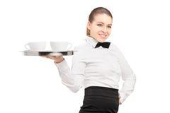 Eine Kellnerin mit der Fliege, die einen Behälter mit Kaffeetassen auf ihm hält Stockfoto