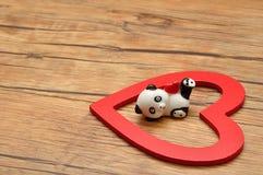 Eine keramische Pandafigürchen mit einem roten Herzen Stockfoto