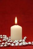 Eine Kerze auf rotem Samthintergrund Lizenzfreie Stockfotografie