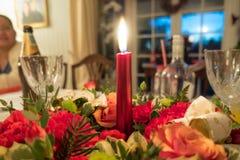 Eine Kerze brennt mitten in einem Blumentabellenmittelstück Lizenzfreies Stockbild