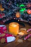 Eine Kerze brennt unter dem Weihnachtsbaum, ist nahe Plätzchen, Süßigkeit, Wollsocken und Handschuhe stockfoto