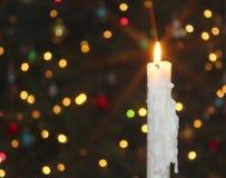 Eine Kerze der weißen Weihnacht mit unscharfen Lichtern Lizenzfreies Stockbild