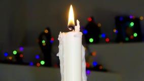 Eine Kerze der weißen Weihnacht mit unscharfen Lichtern Stockbilder