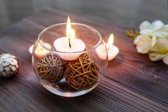 Eine Kerze in einem Glasvase, in einer Dekoration und in verschiedenen interessanten Elementen Kerzen Brennen Stockfotos