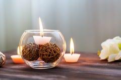 Eine Kerze in einem Glasvase, in einer Dekoration und in verschiedenen interessanten Elementen Kerzen Brennen Lizenzfreies Stockfoto