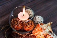 Eine Kerze in einem Glasvase, in einer Dekoration und in verschiedenen interessanten Elementen Kerzen Brennen Lizenzfreie Stockfotos