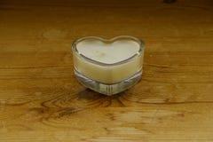 Eine Kerze in geformtem Glas des Herzens stockfotografie