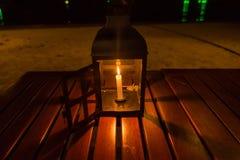 Eine Kerzenlampe auf einer Tabelle durch das Meer nachts lizenzfreie stockfotos