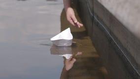Eine Kind-` s Hand startet ein Papierboot zum Fluss im Sommer in der Zeitlupe stock footage