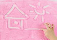 Eine Kind-` s Hand zeichnet ein Haus des Sonnenscheins vom dekorativen Sand Stockbild