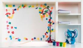 Eine Kind-` s Schulbank mit bunten Farben, Buchstaben und Zahlen, ein Stift, Bleistift, Kompass, Schreibtischlampe und ein weißes Stockbilder