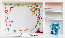 Eine Kind-` s Schulbank mit weißem Hintergrund, bunten Buchstaben und Zahlen, Stift, Bleistift, Elefant füllte Spielzeug an Lizenzfreies Stockfoto