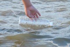 Eine Kinderhand, die eine Plastikflasche Trinkwasser vom Seestrand hält stockfotografie