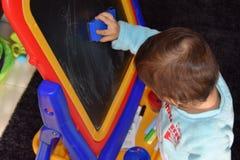 Eine Kinderzeichnung auf dem Brett mit Kreide Stockbild