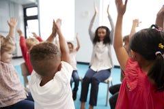 Eine Klasse Säuglingsschulkinder, die auf Stühlen in einem Kreis im Klassenzimmer, Hände mit ihrem weiblichen Lehrer anhebend, na stockfotografie