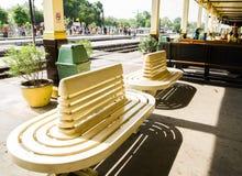 Eine klassisch gebogene Designparkbank in der Gelbcreme in der Bahnhofsplattform Ayutthaya stockfotos