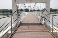 Eine kleine Brücke über dem Fluss am sonnigen Tag stockfotos