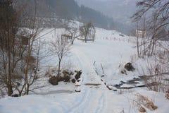 Eine kleine Brücke über dem gefrorenen Fluss lizenzfreie stockfotografie