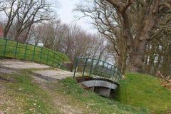 Eine kleine Brücke über a mit wassergefüllter Grabung stockbild