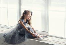 Eine kleine entzückende junge Ballerina in einer spielerischen Stimmung im Inter- Lizenzfreie Stockfotos