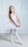 Eine kleine entzückende junge Ballerina in einer spielerischen Stimmung im Inter- Stockfoto