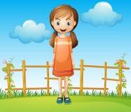 Eine kleine Frau, die nahe dem Bretterzaun steht Stockfotos