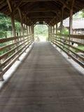 eine kleine Holzbrücke mit einem mit Ziegeln gedeckten Dach, zum von einem kleinen Fluss zu kreuzen lizenzfreies stockfoto