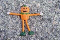 Eine kleine orange Halloween-Kürbispuppe auf der Straße Lizenzfreie Stockbilder