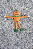 Eine kleine orange Halloween-Kürbispuppe auf der Straße Lizenzfreie Stockfotografie