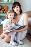 Eine kleine süße kleine blonde Tochter sitzt an ihrem Mutter ` s Schoss, liest ein Buch und lächelt Stockfotografie
