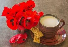 Eine kleine Schale Milch, Brotstöcke und ein heller Blumenstrauß roten PO Lizenzfreie Stockfotografie