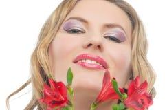 Eine kleine stolze Frau mit klaren roten frischen Blumen Stockfotografie
