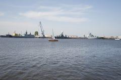 Eine kleine Yacht auf dem Hintergrund von Kriegsschiffen Petrovskaya Gavan, Kronshtadt Lizenzfreie Stockfotografie