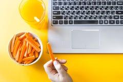 Eine Kleinigkeit essen mit gesundem Lebensmittel am Laptop Stockfoto