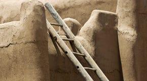 Eine Klotz-Leiter lehnt sich an einer Stuck-Wand Lizenzfreie Stockfotos
