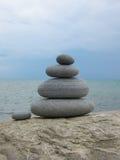 Eine Komposition von fünf Steinen auf einem Rock gegen den Hintergrund O Stockbilder