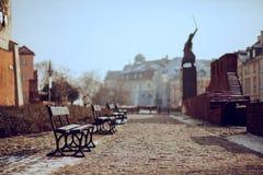 Eine Kopfsteingasse mit Niederlassungen und ein Monument mit Säbel im Hintergrund Stockbild