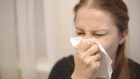 Eine kranke Frau von mittlerem Alter niest und brennt ihre Nase in einem Taschentuch durch stock footage