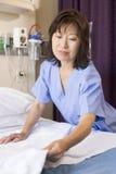 Eine Krankenschwester, die ein Bett bildet lizenzfreie stockfotografie