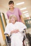 Eine Krankenschwester, die eine ältere Frau in einem Rollstuhl drückt stockbild