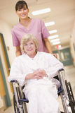 Eine Krankenschwester, die eine ältere Frau in einem Rollstuhl drückt lizenzfreies stockfoto