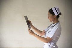 Eine Krankenschwester, die Röntgenstrahlen betrachtet Stockfoto