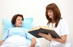 Eine Krankenschwester, die zu einem Patienten liest Lizenzfreie Stockfotografie