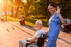 Eine Krankenschwester grüßt jemand Hinter ihr im Rollstuhl sitzt einen alten Mann und lächelt Stockfotografie