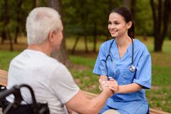 Eine Krankenschwester ist lächelnd halten und die Hand eines alten Mannes, der nahe bei herein einem Rollstuhl im Park sitzt Stockbild
