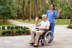 Eine Krankenschwester und ein alter Mann, der in einem Rollstuhl glücklich sitzt, grüßen jemand Stockbilder
