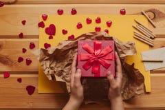 Eine kreative Person verpackt ein handgemachtes Geschenk in einem schönen roten Kasten, der mit einem Band gebunden wird Lizenzfreie Stockfotos