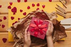 Eine kreative Person verpackt ein handgemachtes Geschenk in einem schönen roten Kasten, der mit einem Band gebunden wird Stockfotografie