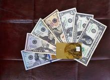 Eine Kreditbankkarte steht auf einem Satz Dollar auf dem Hintergrund eines Lederstuhls still Lizenzfreies Stockbild